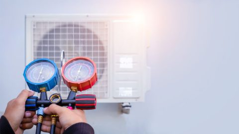 HVAC technician measuring AC refrigerant levels